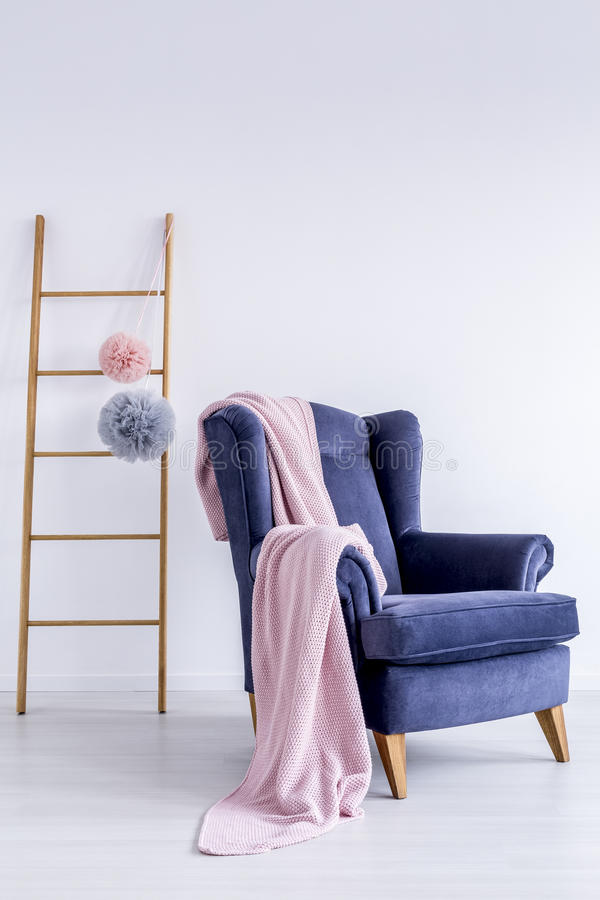 Pink blanket on blue armchair stock image