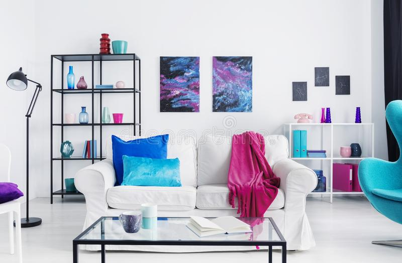 Pink blanket and blue cushions on white sofa in loft interior with table, lamp and posters. Real photo stock image