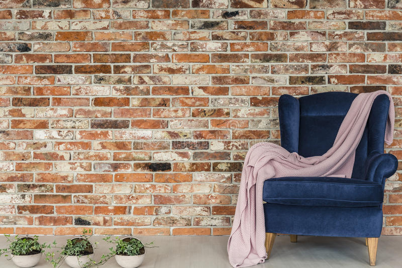 Pink blanket lying on armchair. Brick wall, pink blanket lying on blue armchair royalty free stock image