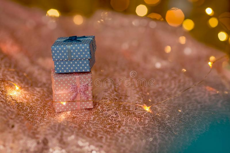 A pink and blue gifts on a coral shiny background. stock image