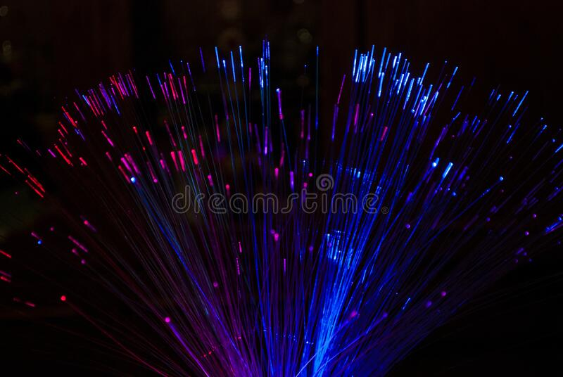 Pink and blue glow sticks on a black background stock image