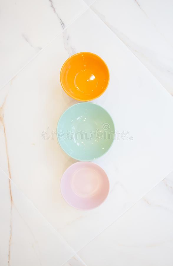Plates on white marble. bowls without food of different colors, top view, flat layout. pink, blue, orange stock images