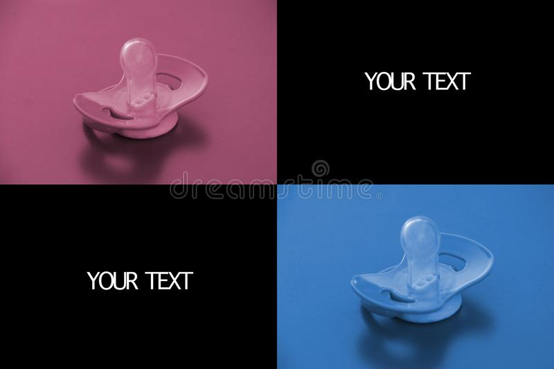 Pink and blue pacifier on corner, black background behind, copy space for your text stock photo