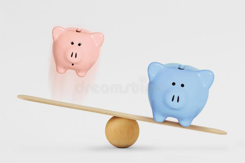 Pink and blue piggy bank on balance scale - Gender pay gap concept stock photos