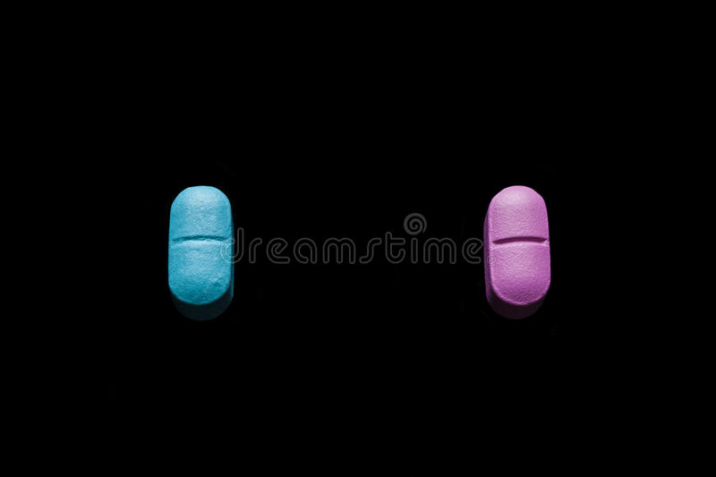 Pink and blue pills on black background from high angle royalty free stock image