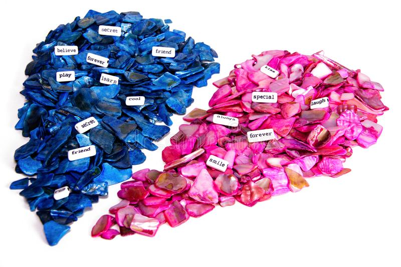 Pink and blue rock divided heart coming together. Concept two halves creating a romantic union or friendship with scattered words stock images