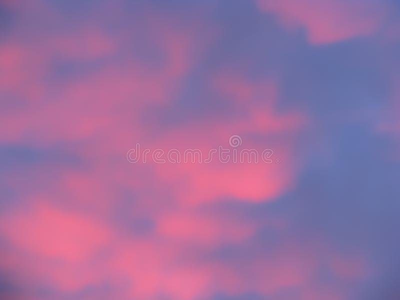 Pink clouds and blue sky soft focus background. Pink and blue sky background. Soft focus fluffy pink clouds on a blue sky at sunset stock photo