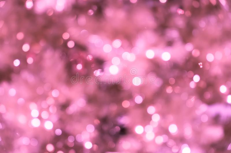 Pink blurred background with bokeh lights/closeup of blurred pink Christmas tree with lights.  royalty free stock photo
