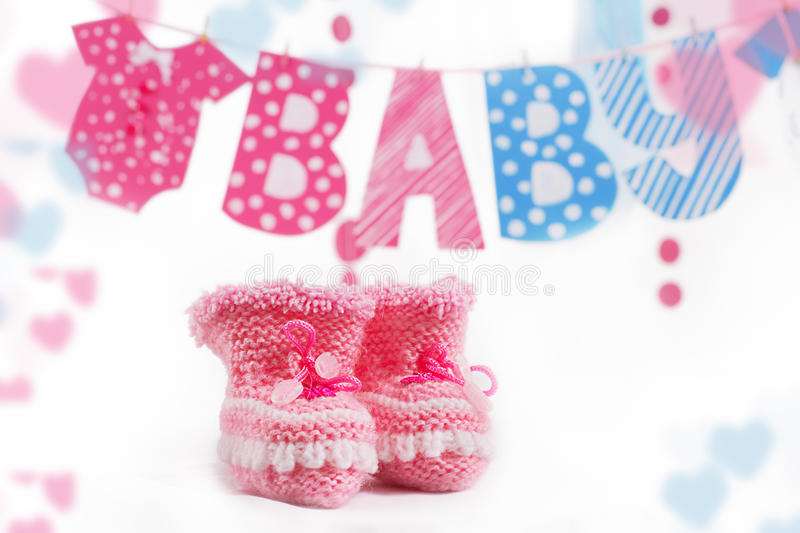 Pink bootees and baby word garland. As decoration stock images