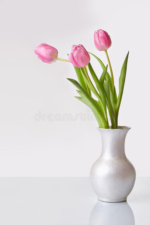 Pink bouquet of tulips in a vase royalty free stock photography