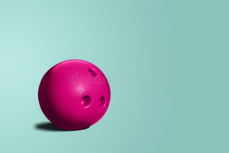 Pink bowling ball. A toy bowling ball of pink color on a blue, turquoise pastel background. A minimalist concept, abstract. The concept of having fun, going out royalty free stock photos