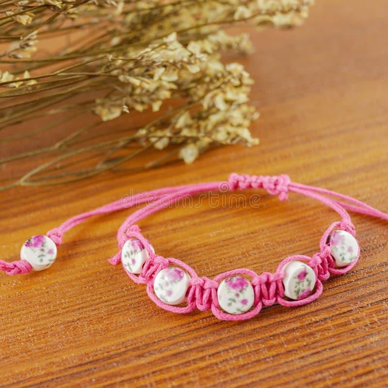 Pink bracelet on wooden background stock photo