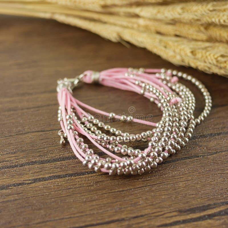 Pink bracelet on wooden background royalty free stock photography