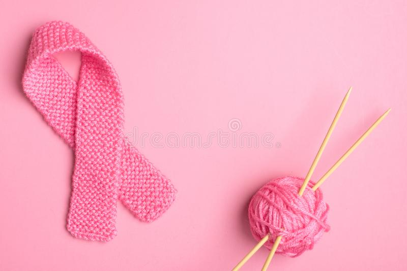 Pink Breast Cancer Awareness Symbol knitted in pink yarn with ball of yarn and needles on sides with center room or space for copy. Text or your words stock photo