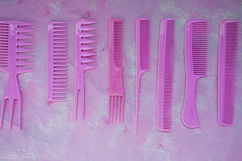 Pink bright comb for hairdressers. Beauty saloon. Tools for hairstyles. Colorful pink background. Barbershop. A set of different royalty free stock photos