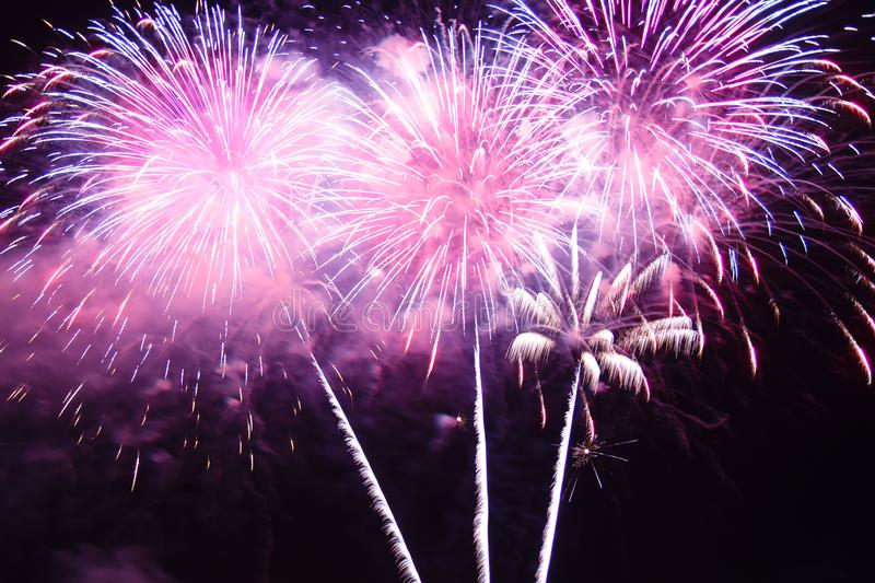 Pink bright sparks of festive fireworks in the night sky. Horizontal photo royalty free stock photo