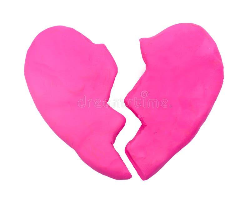 Pink broken heart shape plasticine clay stock images