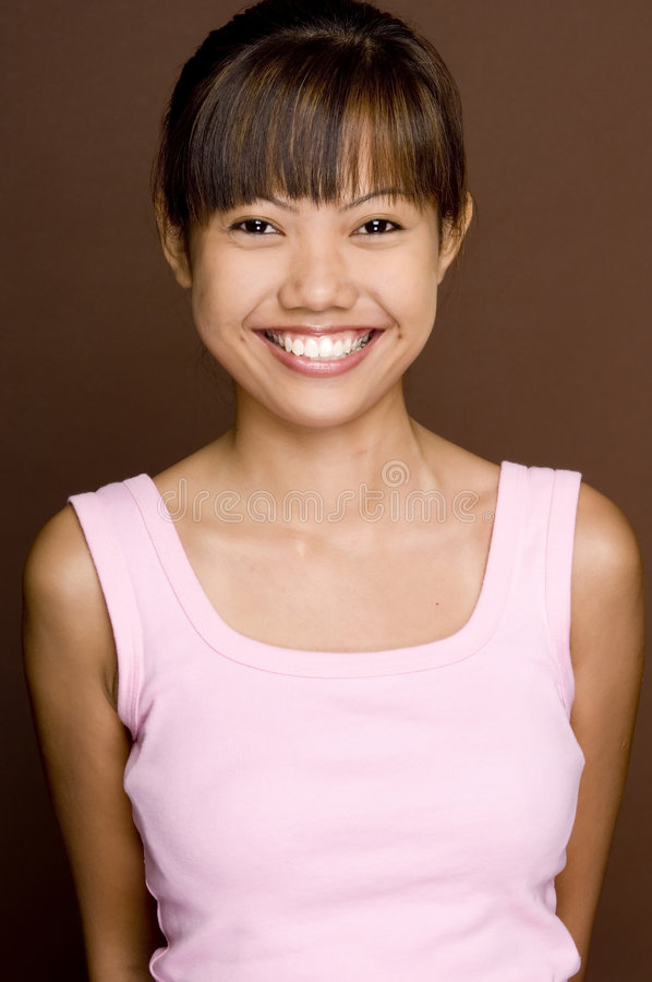 Pink On Brown 6. A cute young asian woman with a great smile in pink on brown background stock photography
