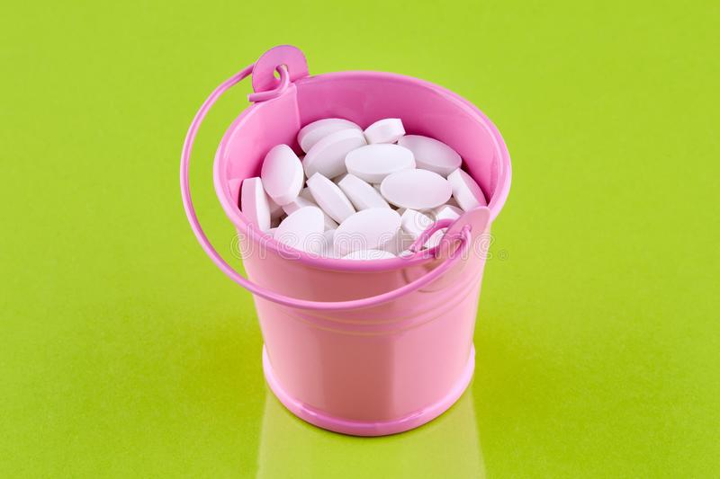 Pink bucket with white pills on green background.  royalty free stock photos