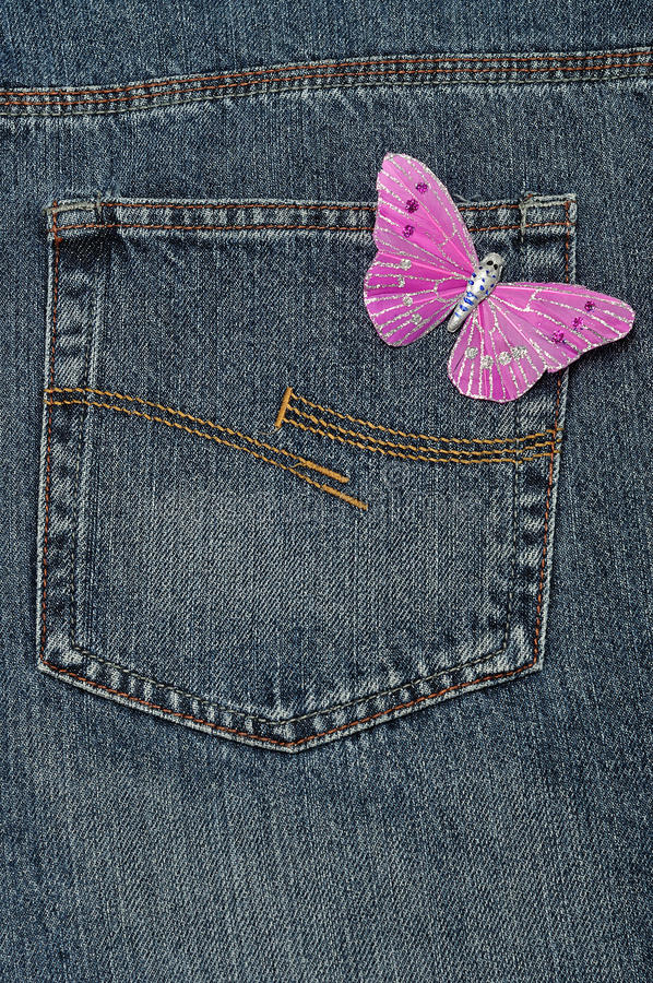 A pink butterfly made out of silk. Displayed on a back pocket of a denim jean royalty free stock photos