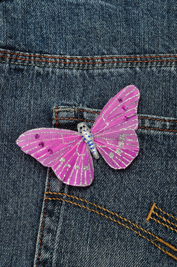 A pink butterfly made out of silk. Displayed on a back pocket of a denim jean stock image