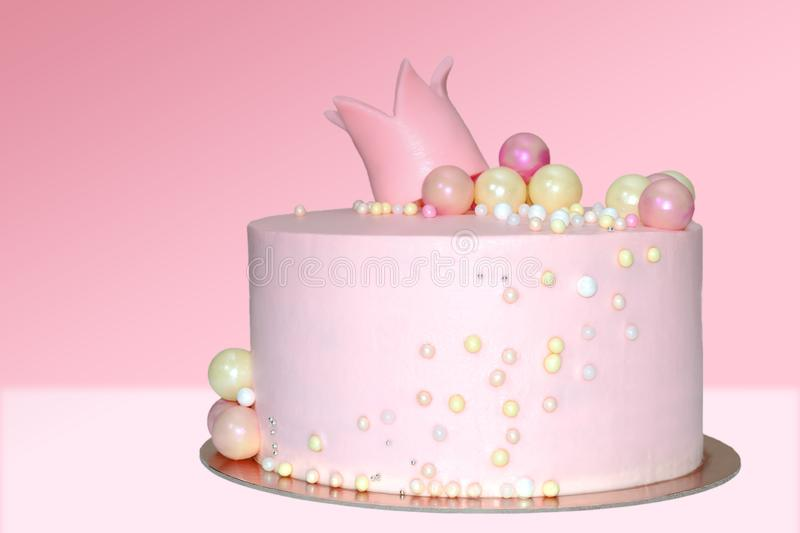 Pink cake for a girl with a decoration in the form of a crown and balls on an isolated background. Pink cake for a girl with a decoration in the form of a crown stock photos