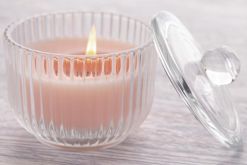 Pink candle burning in a glass beaker on an old white wooden table. A pink candle is burning in a glass cup on an old white wooden table. Nearby is the lid of stock photo