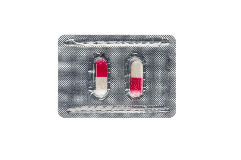 Pink capsules in a blister pack isolated on white. Capsules in a blister pack isolated on white background royalty free stock photography