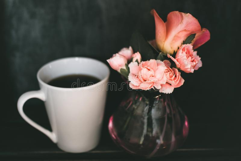 Pink Carnation Flower and Pink Rose Flower in Clear Glass Vase Beside Mug of Coffee royalty free stock images