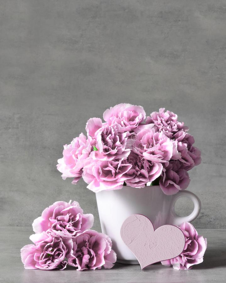 Pink carnation flowers in cup and heart on grey background royalty free stock photography