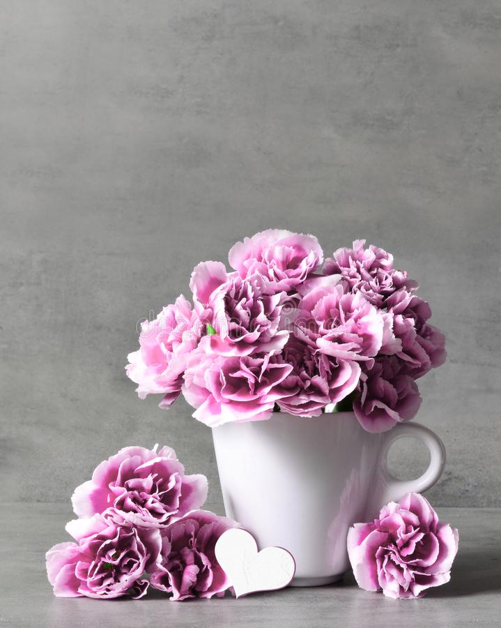Pink carnation flowers in cup and heart on grey background. royalty free stock images