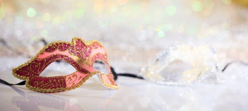 Pink carnival mask on bokeh background. Pink carnival mask on white surface, abstract bokeh background royalty free stock photo