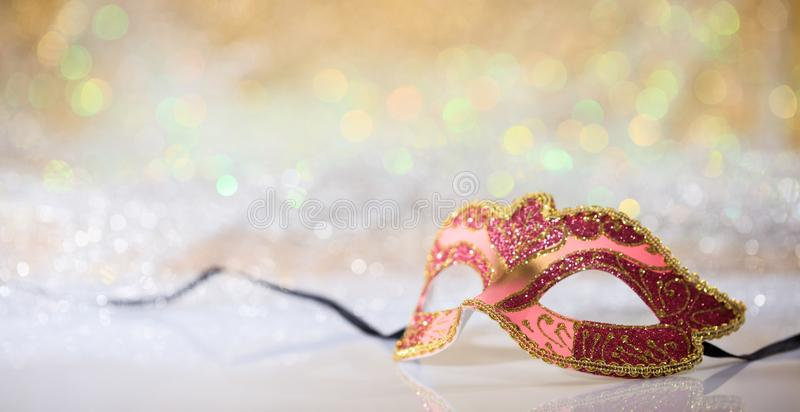 Pink carnival mask on bokeh background. Pink carnival mask on white surface, abstract bokeh background royalty free stock images
