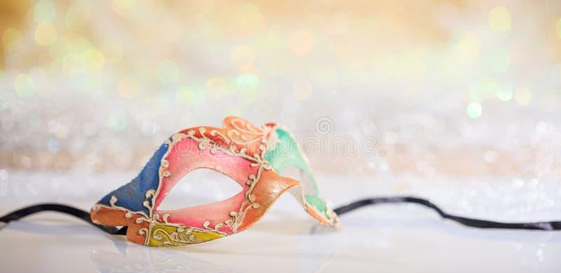 Pink carnival mask on bokeh background. Pink carnival mask on white surface, abstract bokeh background stock photo