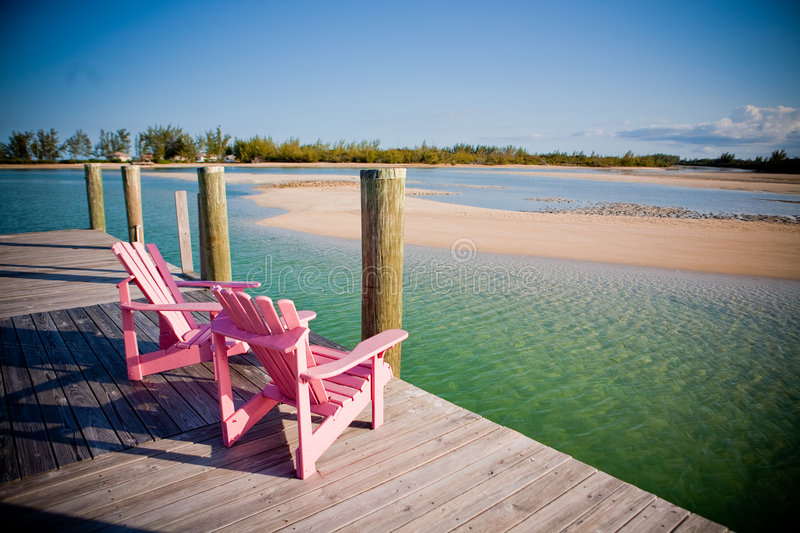 Pink Chairs. Faced toward the sun at end of a dock stock photos