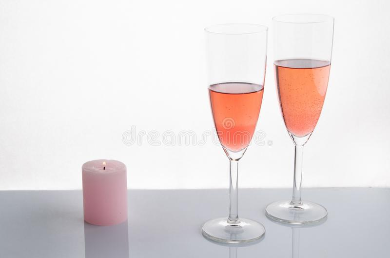 Pink champagne with pink candle. On a white background stock photos