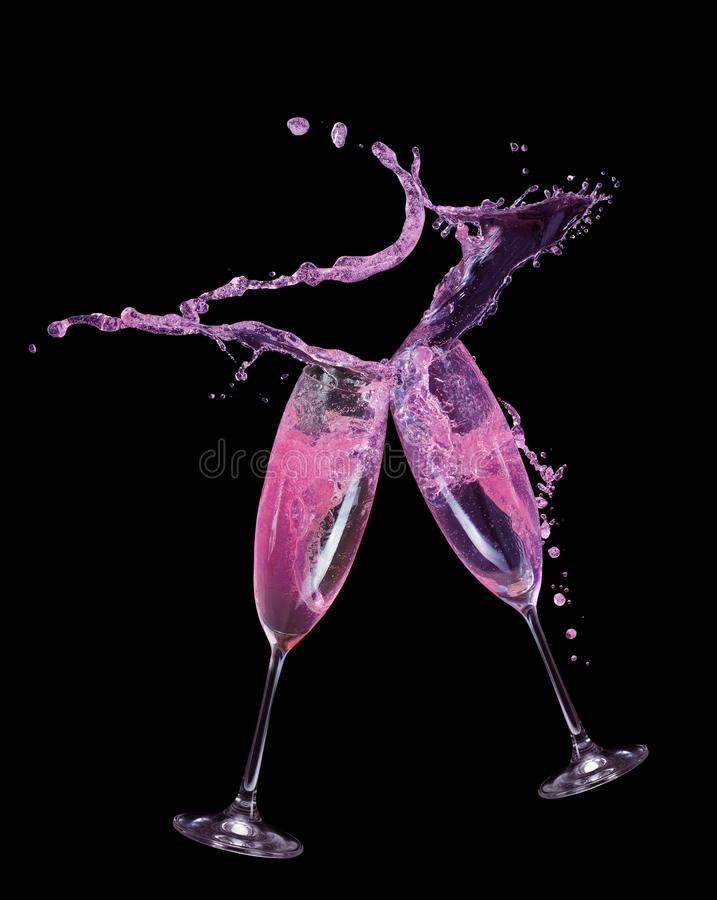 Pink champagne splash in glass on a black background.  stock images