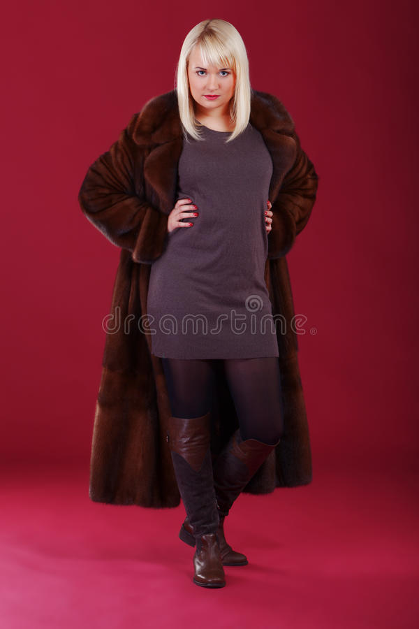 Pink chic. Girl in winter coat on pink background stock photography