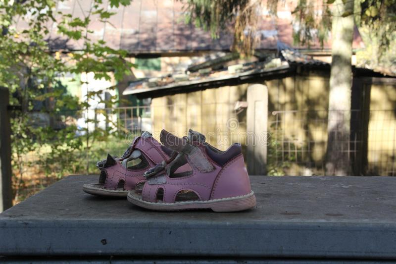 Forgotten shoes. Pink children shoes royalty free stock image