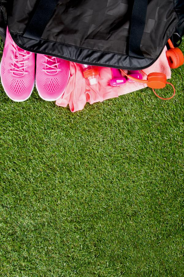 Pink clothes and accessories for fitness, a bottle of water, in a black sports bag, on the background of grass stock photo