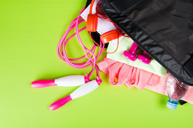 Pink clothes and accessories for fitness, a bottle of water, a notebook for writing, in a sports bag, on a light green background royalty free stock photos