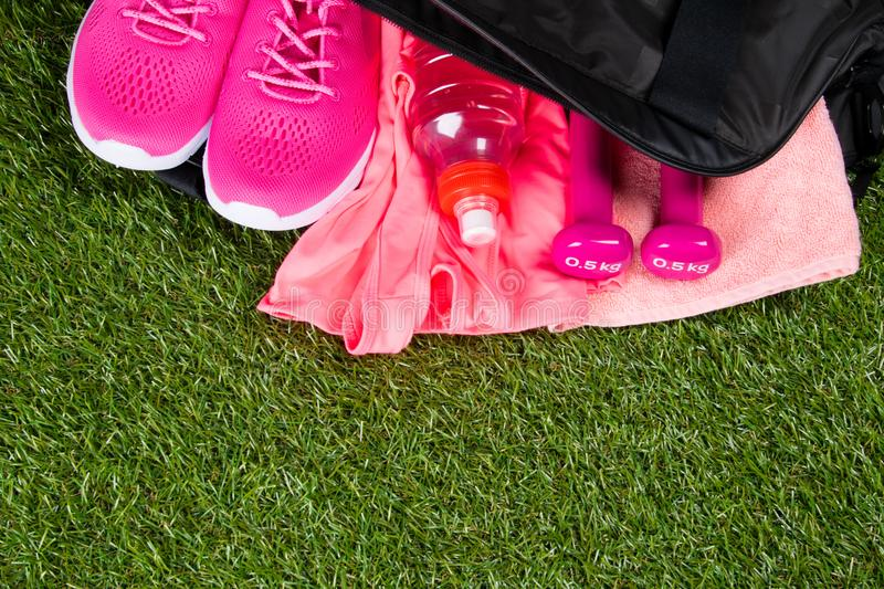 Pink clothes and accessories for fitness, a bottle of water, in a sports bag, on the background of grass royalty free stock images