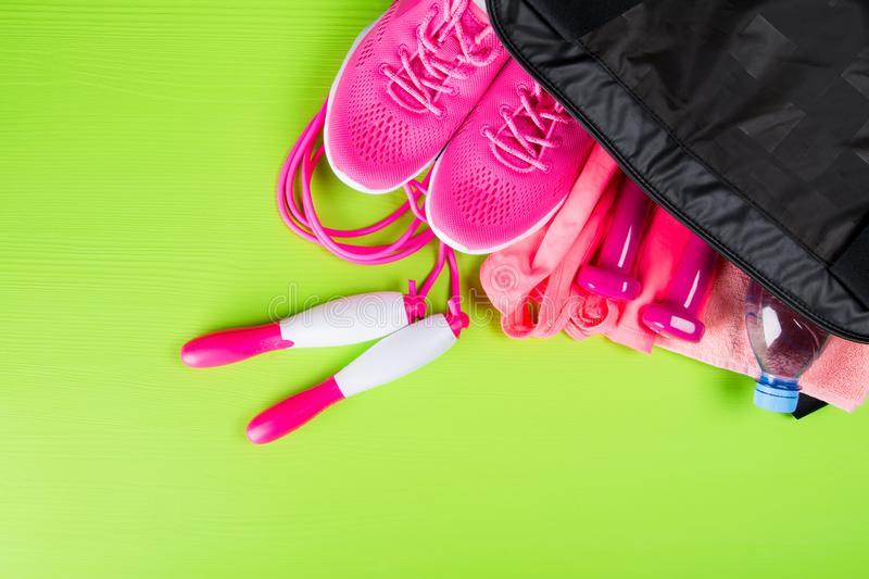 Pink clothes and accessories for fitness, a bottle of water, in a sports bag, on a light green background royalty free stock photos