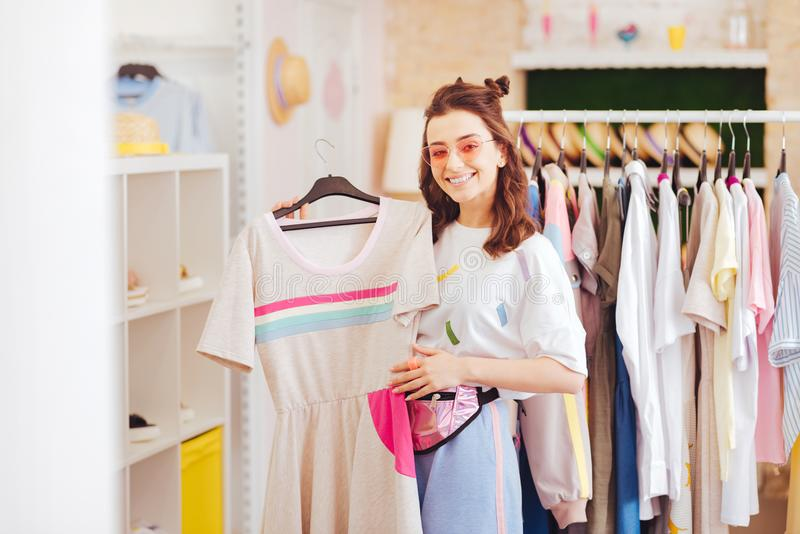 Beaming woman being fond of pink clothes buying new dress. Pink clothes. Beaming good-looking woman being fond of pink clothes buying new dress in favorite shop stock photos