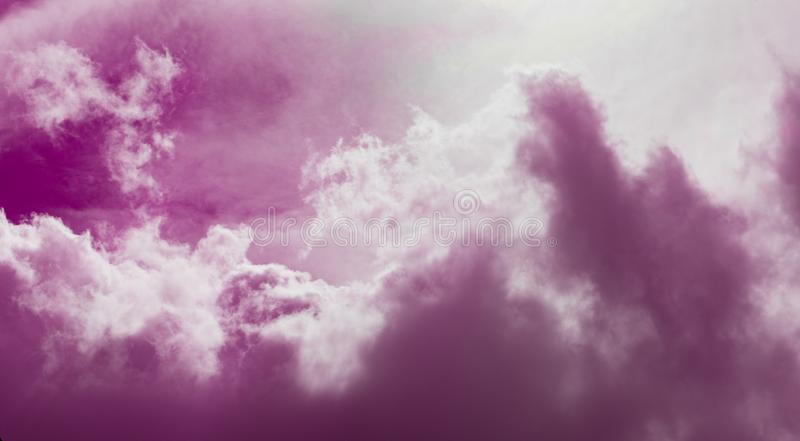 Pink and Clouds Background. Puffy white clouds on pink sky background stock photo