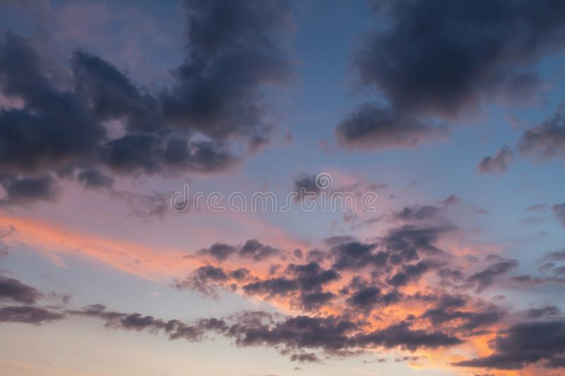Pink clouds and blue skies background. Beautiful clouds and blue sky background at sunset with pink and purple tones over England UK. Cloudscape and skyscape stock image