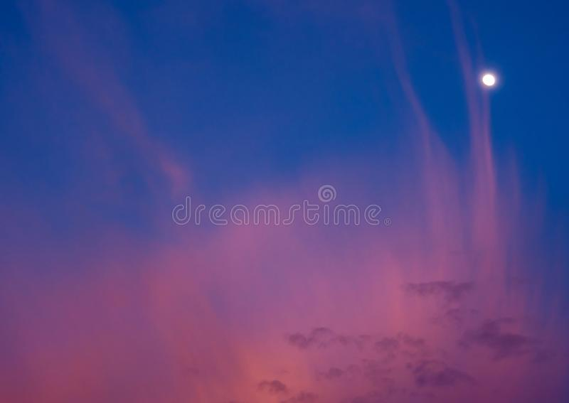 Clouds and moon in sunset sky. Pink clouds and moon in sunset sky stock images