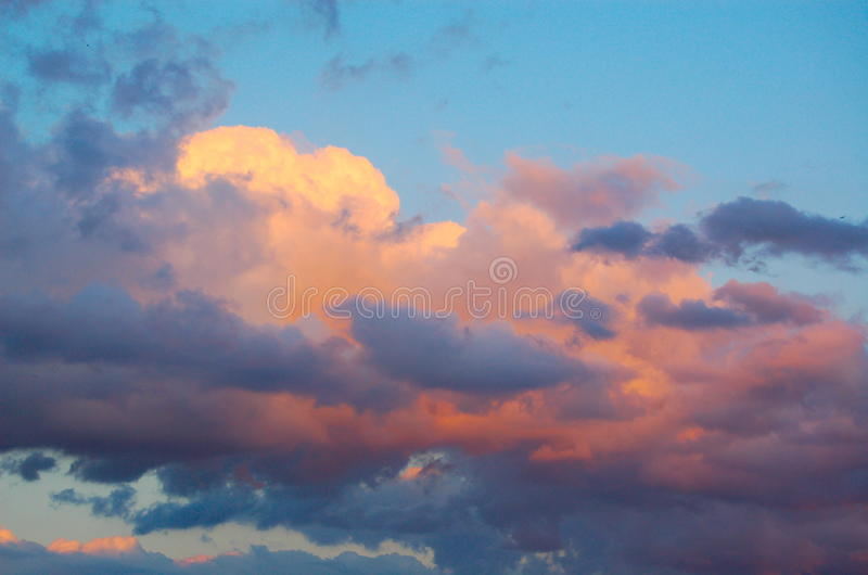 Pink clouds at sunset. Billowing clouds in a blue sky reflect pink tones at sunset royalty free stock photos