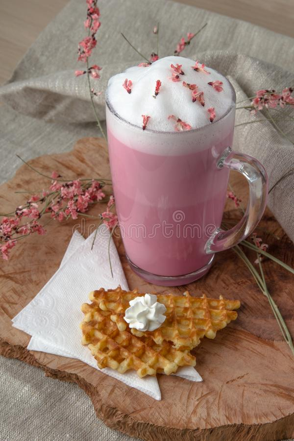 Pink coffee latte macchiato with foamy flowers decorated royalty free stock image