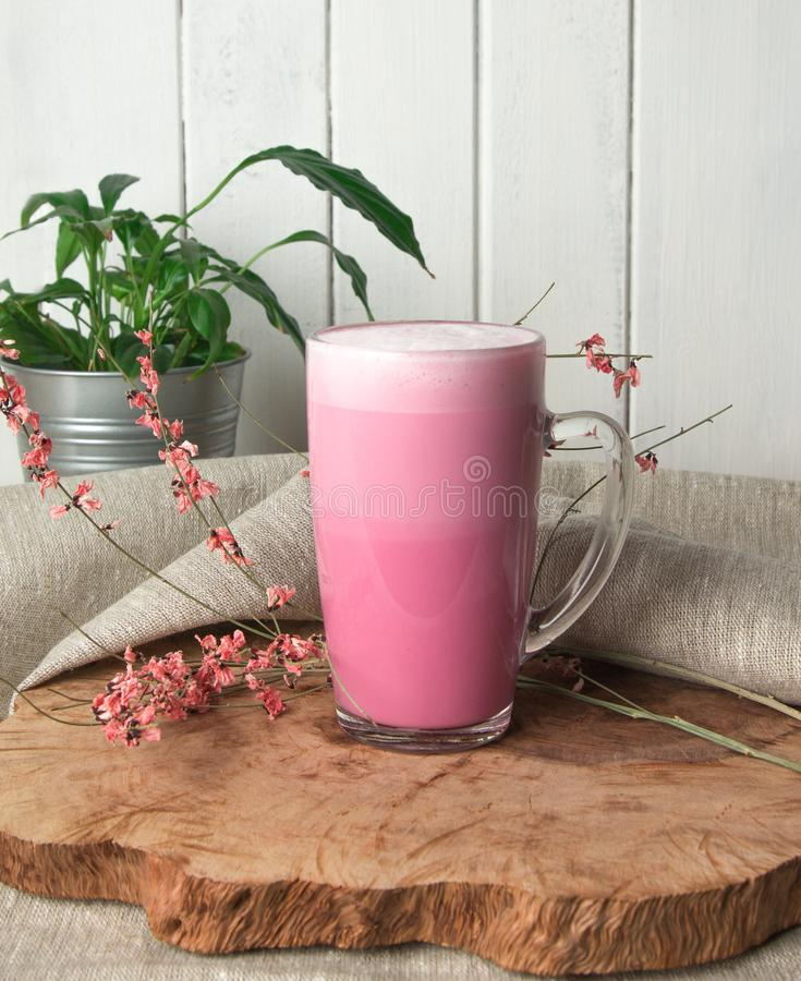 Pink coffee latte macchiato in a glass cup on a wooden backing decorated with dried flower. S with air foam stock photo